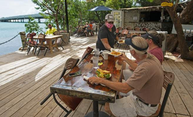 In this photo provided by the Florida Keys News Bureau, Alexeen Simms, a server at the Hungry Tarpon Restaurant in Islamorada, Fla., provides a luncheon entree to a couple Monday. June 1. 2020. After being closed to visitors since March 22, 2020, to help curtail the spread of COVID-19, the Florida Keys reopened to tourists Monday. Tourism employs about 45 percent of the Keys workforce. (Andy Newman/Florida Keys News Bureau via AP)