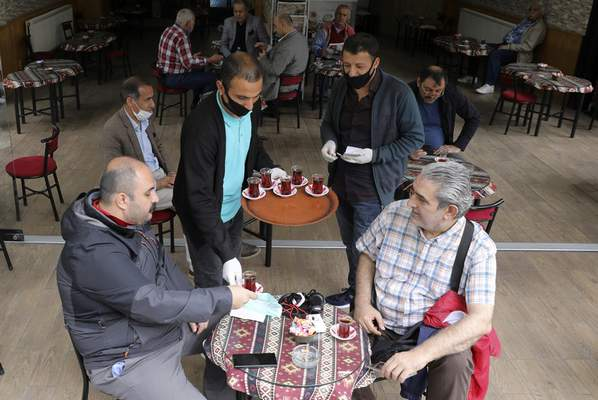 Waiters wearing face masks to protect against coronavirus, serves clients at a theahouse, in Ankara, Turkey, Monday, June 1, 2020. Restaurants and cafes welcomed sit-in customers, beaches and museums reopened as Turkey's broadest easing of coronavirus restrictions came into effect.(AP Photo/Burhan Ozbilici)