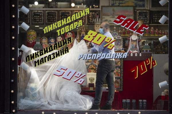 An employee removes a plastic cover from goods at the shop window after reopening in Moscow, Russia, on Monday, June 1, 2020. Monday's reopening of retail stores along with dry cleaners and repair shops comes as the pace of contagion has stabilized in the Russian capital that has accounted for about half of the nation's infections. (AP Photo/Alexander Zemlianichenko Jr)