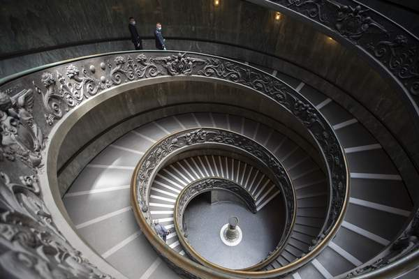 Museum employees, wearing masks to prevent the spread of coronavirus, walk down a staircase designed by Giuseppe Momo in 1932, inspired by the original Bramante staircase designed by Renaissance architect Donato Bramante, as the Vatican Museum reopened, in Rome, Monday, June 1, 2020. The Vatican Museums reopened Monday to visitors after three months of shutdown following COVID-19 containment measures. (AP Photo/Alessandra Tarantino)