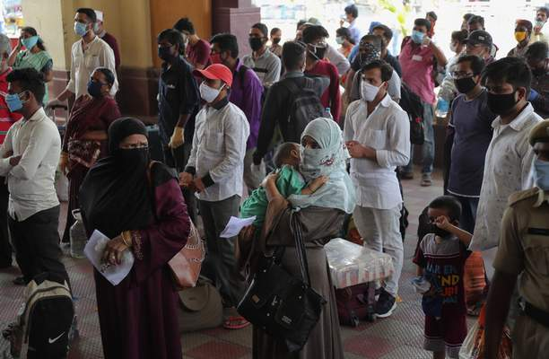 Passengers wait outside Hyderabad Railway Station to catch a train to return to their home states in Hyderabad, India, Monday, June 1, 2020. More states opened up and crowds of commuters trickled onto the roads in many of India's cities on Monday as a three-phase plan to lift the nationwide coronavirus lockdown started despite an upward trend in new infections. (AP Photo/Mahesh Kumar A.)