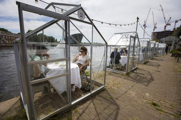 Customers seated in small glasshouses enjoy lunch at the Mediamatic restaurant in Amsterdam, Netherlands, Monday, June 1, 2020. The government took a major step to relax the coronavirus lockdown, with bars, restaurants, cinemas and museums reopening under strict conditions, abiding by government guidelines and respecting social distancing to help curb the spread of the COVID-19 coronavirus. (AP Photo/Peter Dejong)