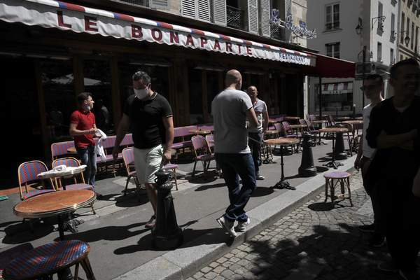 Waiters prepare the terrace of a restaurant in Paris, Monday, June 1, 2020, as France gradually lifts its Covid-19 lockdown. France is reopening tomorow its restaurants, bars and cafes as the country eases most restrictions amid the coronavirus crisis. (AP Photo/Christophe Ena)