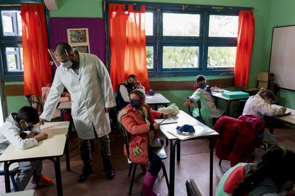 Wearing face masks amid the new coronavirus pandemic, a teacher leads his class on the first day back to a rural school near Empalme Olmos, Uruguay, Monday, June 1, 2020, as Uruguay's total lockdown begins to ease. (AP Photo/Matilde Campodonico)