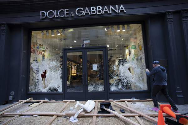 A passerby photographs a smashed Dolce and Gabbana store window in the SoHo neighbourhood of New York, Monday, June 1, 2020. Protesters broke into the store Sunday night in reaction to George Floyd's death while in police custody on May 25 in Minneapolis. (AP Photo/Mark Lennihan)
