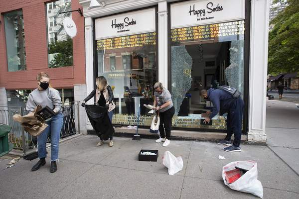 Neighbourhood volunteers clean up broken glass at a Happy Socks store in the SoHo neighbourhood of New York, Monday, June 1, 2020. Protesters broke into the store Sunday night in reaction to George Floyd's death while in police custody on May 25 in Minneapolis. (AP Photo/Mark Lennihan)