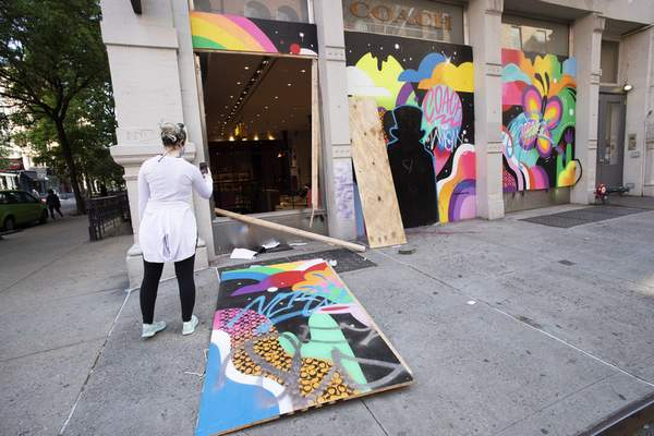 A passerby photographs a ransacked Coach store in the SoHo neighbourhood of New York, Monday, June 1, 2020. Protesters broke into the store Sunday night in reaction to George Floyd's death while in police custody on May 25 in Minneapolis. (AP Photo/Mark Lennihan)