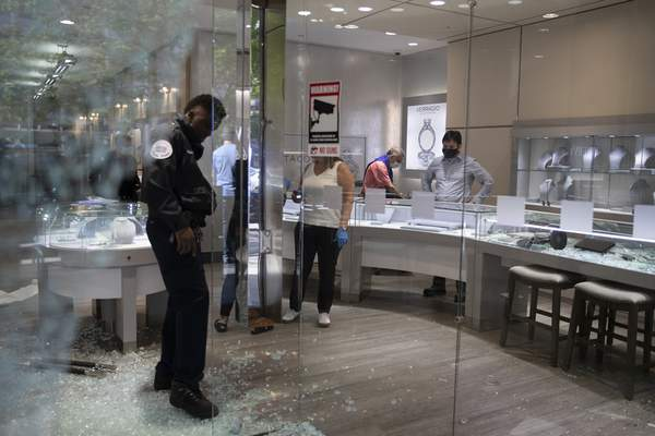 Shattered window and door glass is scattered on the floor inside Mervis Diamond Importers in Washington, Monday, June 1, 2020, after a night of protests over the death of George Floyd. Floyd died after being restrained by Minneapolis police officers. (AP Photo/Carolyn Kaster)