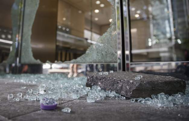 Shattered window and door glass from Mervis Diamond Importers is scattered on sidewalk in Washington, Monday, June 1, 2020, after a night protests over the death of George Floyd. Floyd died after being restrained by Minneapolis police officers on May 25. (AP Photo/Carolyn Kaster)