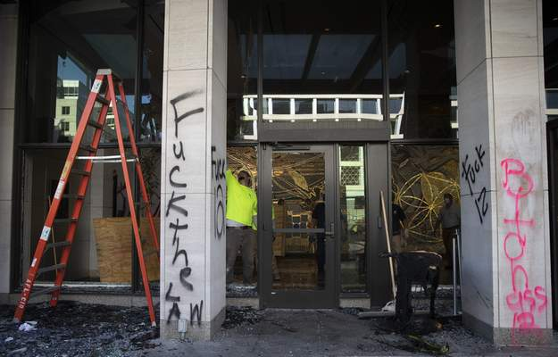 EDS NOTE: OBSCENITY - Windows and doors are shattered and spray paint covers the from of the AFL-CIO building in Washington, Monday, June 1, 2020, after a night of protests over the death of George Floyd. Floyd died after being restrained by Minneapolis police officers on May 25. (AP Photo/Carolyn Kaster)