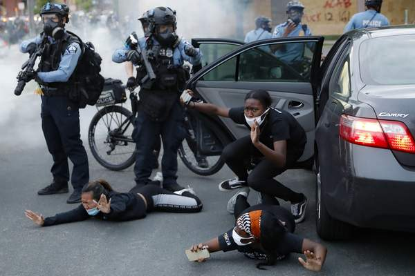 Motorists are ordered to the ground from their vehicle by police during a protest on South Washington Street, Sunday, May 31, 2020, in Minneapolis. (AP Photo/John Minchillo)