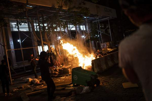 Protesters start fires along the SoHo shopping district on Sunday, May 31, 2020, in New York. (AP Photo/Wong Maye-E)