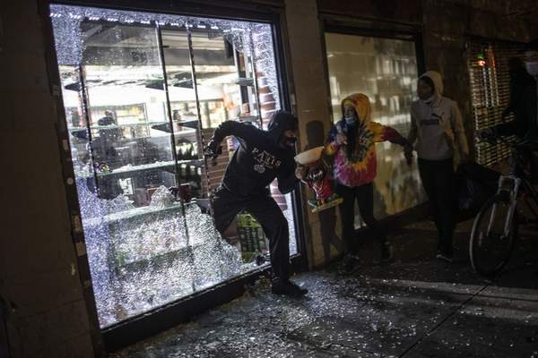 People run out of a smoke shop with smoking instruments after breaking in as police arrive on Monday, June 1, 2020, in New York. (AP Photo/Wong Maye-E)