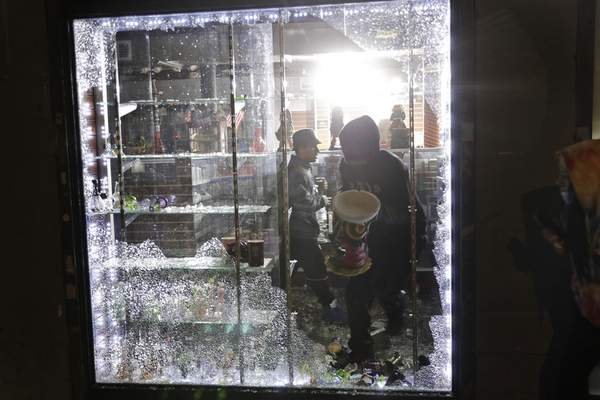 People carry things out of a smoke shop through a broken window in New York, Monday, June 1, 2020. (AP Photo/Seth Wenig)