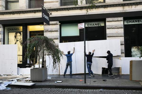 Workers board up the windows of a Chanel store Monday, June 1, 2020, following protests in the SoHo neighborhood of New York. (AP Photo/Mark Lennihan)