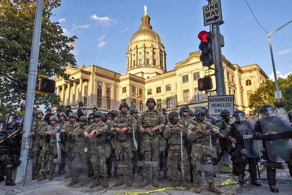 Authorities stand guard in the area around the Georgia state Capitol as protests continued for a third day in Atlanta on Sunday, May 31, 2020. (Ben Gray/Atlanta Journal-Constitution via AP)