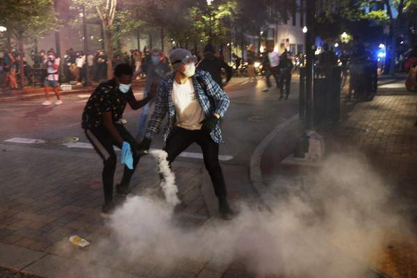A protester tosses a smoke bomb towards police during a third night of unrest Sunday May 31, 2020, in Richmond, Va. Gov. Ralph Northam issued a curfew for this evening. (AP Photo/Steve Helber)