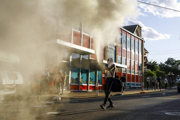 A person shoots a fire extinguisher into the air as he walks though a street in Upper Darby, Pa. on Sunday May 31, 2020, as people move through streets in protest over the death of George Floyd, a black man who was in police custody in Minneapolis. (AP Photo/Matt Slocum)