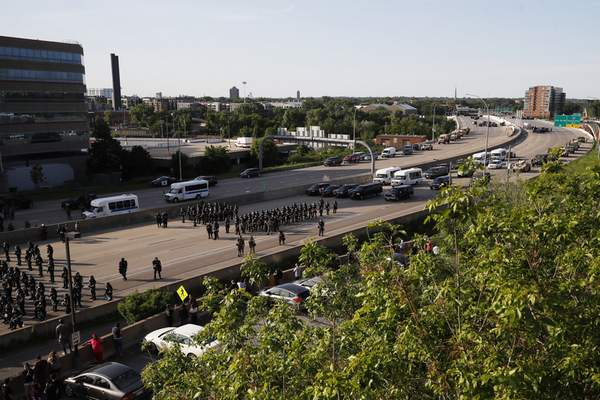 A police force prepares to clear an interstate of demonstrators Sunday, May 31, 2020, in Minneapolis. (AP Photo/John Minchillo)