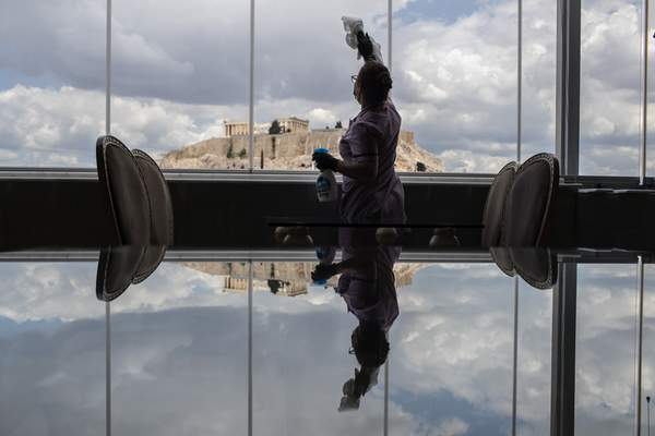 Associated Press With the ancient Acropolis visible through the window, a worker cleans glass in a dining area at the Acropolian Spirit Hotel in central Athens, Greece. Lockdown restrictions were lifted on the nation's hotels Monday.