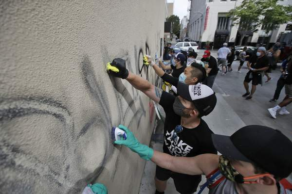 Associated Press Volunteers clean graffiti from a store wall Monday in Santa Monica, Calif., a day after protests.