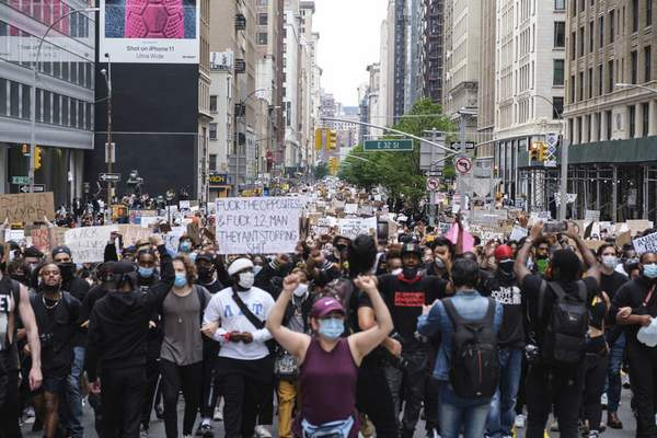 Protesters raise their fist as they march through midtown as part of a demonstration Tuesday, June 2, 2020, in New York, to protest the death of George Floyd, who died May 25 after he was pinned at the neck by a Minneapolis police officer. (AP Photo/Yuki Iwamura)