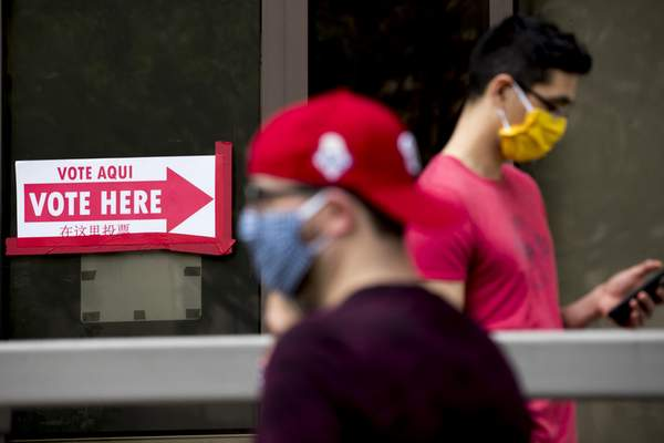 People wear masks as they wait in line to vote at a voting center during primary voting in Washington, Tuesday, June 2, 2020. (AP Photo/Andrew Harnik)