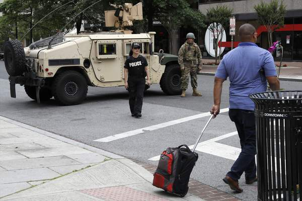 A man walks through an intersection blocked by a military humvee from DC National Guard and a DEA police officer as demonstrators gather to protest the death of George Floyd, Tuesday, June 2, 2020, in Washington. Floyd died after being restrained by Minneapolis police officers. (AP Photo/Jacquelyn Martin)