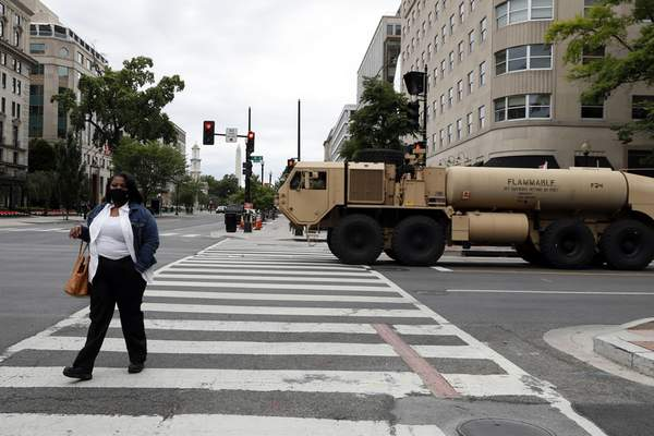 A woman walks across K Street as a military fuel truck passes by as demonstrators continue to protest the death of George Floyd, Tuesday, June 2, 2020, near the White House in Washington. (AP Photo/Jacquelyn Martin)