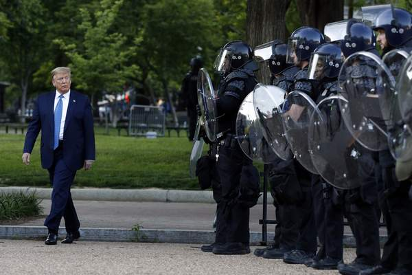 President Donald Trump walks past police in Lafayette Park after he visited outside St. John's Church across from the White House Monday, June 1, 2020, in Washington. (AP Photo/Patrick Semansky)