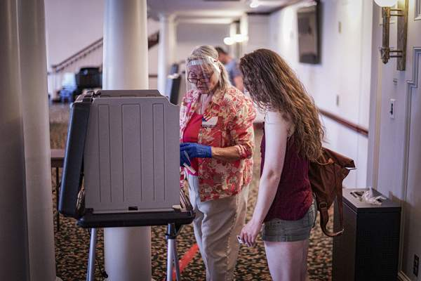 Mike Moore | The Journal Gazette A poll worker wearing a face shield shows a voter how to use the voting machine Tuesday at The Chapel.