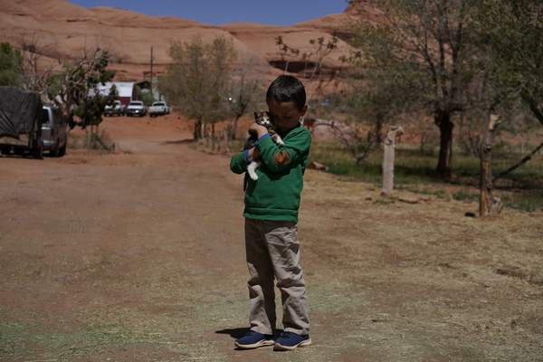 Associated Press A boy holds a kitten in front of his home on the Navajo reservation in Oljato-Monument Valley, Utah,in April.