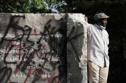 America Protests Alabama Associated Press Robert Walker poses for a photo Tuesdayby what's left of a Confederate memorial in Birmingham, Ala., that the city took down. (Jay ReevesSTF)