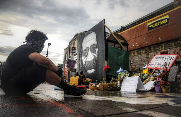 After a new mural, center, of George Floyd is added to a growing memorial of tributes, Trevor Rodriquez sits alone at the spot where Floyd died while in police custody, Tuesday June 2, 2020, in Minneapolis, Minn. I have been out every single night protesting peacefully, just trying to support everything, said Rodriquez. I didn't want to come here just on a rush, so I had to just take a moment to pay my respect. (AP Photo/Bebeto Matthews)