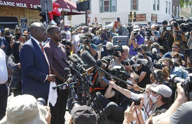 Quincy Mason, son of George Floyd, listens as family attorney Ben Crump, left, addresses a news conference, Wednesday, June 3, 2020, while they and some Floyd family members visited the site in Minneapolis. (AP Photo/Jim Mone)