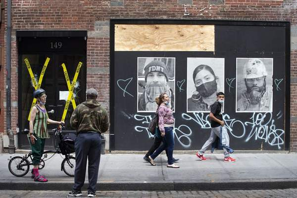 People pass broken windows, left, and photographs of essential workers during the coronavirus pandemic, right, Wednesday, June 3, 2020, in the SoHo neighborhood of New York. (AP Photo/Mark Lennihan)