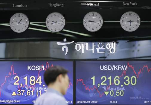South Korea Financial Markets A currency trader walks by the screens showing the Korea Composite Stock Price Index (KOSPI), left, and the foreign exchange rate between U.S. dollar and South Korean won at the foreign exchange dealing room in Seoul, South Korea, Thursday, June 4, 2020. (AP Photo/Lee Jin-man) (Lee Jin-man STF)