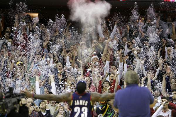 FILE - In this Dec. 25, 2008, file photo, fans toss confetti to mimic Cleveland Cavaliers' LeBron James's pre-game chalk toss before an NBA basketball game against the Washington Wizards in Cleveland. (AP Photo/Mark Duncan, File)