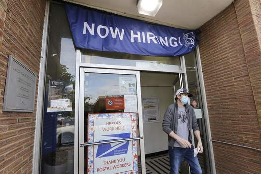In this photo taken Thursday, June 4, 2020, a customer walks out of a U.S. Post Office branch and under a banner advertising a job opening, in Seattle. (AP Photo/Elaine Thompson)