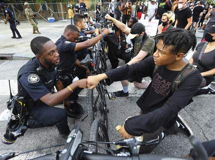 America Protests Black Officers Associated Press Atlanta Police Officer J. Coleman and protester Elijah Raffington fist-bump in a symbolic gesture of solidarity Wednesday at the city's Olympic Park. (Curtis ComptonMBO)