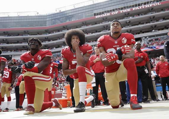 Associated Press Quarterback Colin Kaepernick, center, kneels with 49ers teammates Eli Harold, left, and Eric Reed during the national anthem before a 2016 game. Kaepernick knelt to protest racial injustice.