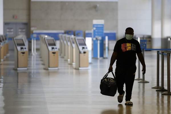 Associated Press A traveler walks in a mostly empty American Airlines terminal at the Los Angeles International Airport late last month. Many airlines are cutting even more jobs to cope with a crushing drop in air travel caused by the coronavirus pandemic.
