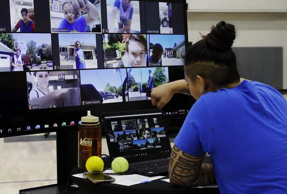 Associated Press VeAnne Navarro has a virtual fist bump with students including Bjarki Robertsson, lower left on screen, of Reykjavik, Iceland, last week at the Golden State Warriors' virtual basketball camp.