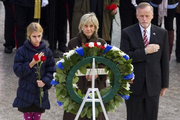FILE - In this Nov. 22, 2013 file photo, An unidentified girl, left, holds a rose during a wreath laying ceremony with former Ambassador to Ireland Jean Kennedy Smith, center, and Patrick Hallinan, executive director of Army National Military Cemeteries, at the grave of John F. Kennedy at Arlington National Cemetery, in Arlington, Va. (AP Photo/Jacquelyn Martin)
