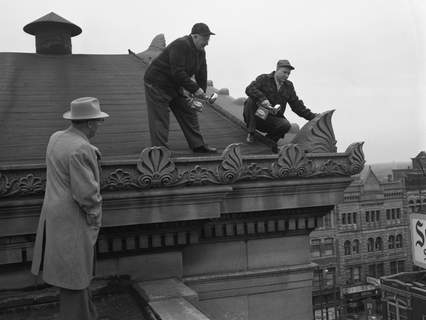 January 1958: P.E. Henebry, president of the Allen County Commissioners, left, watches Jimmie A. Soules and James L. Soules of Bird Repellent Co. examine the roof of the Allen County Courthouse for signs of pigeons and starlings. (Journal Gazette file photo)
