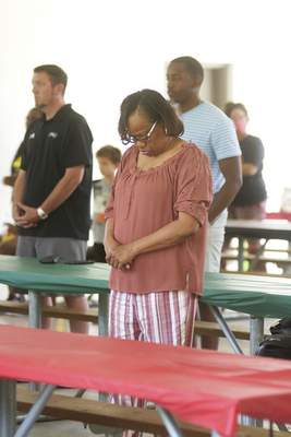 Katie Fyfe | The Journal Gazette  Carolyn Moore bows her head during a moment of silence for George Floyd and ancestors during the Juneteenth Celebration at Foster Park on Friday.