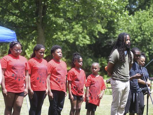 Katie Fyfe | The Journal Gazette  Director of the Art Leadership Center, Mr. Adrian Curry and his student leaders lead an eight minute and forty five second moment of silence for George Floyd and ancestors during the Juneteenth Celebration at Foster Park on Friday.