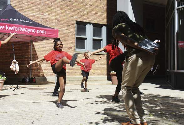 Katie Fyfe | The Journal Gazette  Adrian Curry, director of the Art Leadership Center, and his student leaders practice for their performance for the Juneteenth Celebration at the Keller Willliams courtyard on Friday.