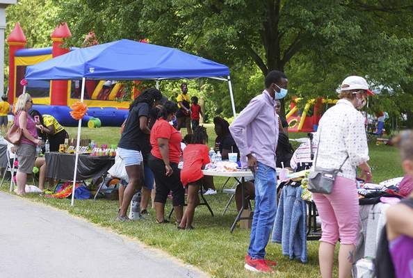 Katie Fyfe | The Journal Gazette  Booths are set up for people to shop at as well as a bouncy house for children during the Juneteenth Celebration at Foster Park on Friday.
