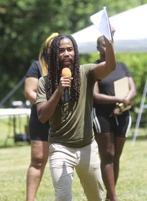 Katie Fyfe | The Journal Gazette  Addrian Curry, director of the Art Leadership Center, leads a Never Forget chant during the Juneteenth Celebration at Foster Park on Friday.
